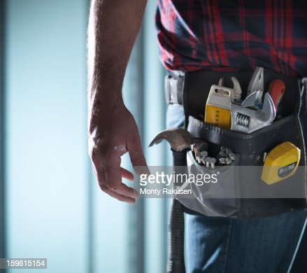 Man wearing tool belt with selection of tools and nails