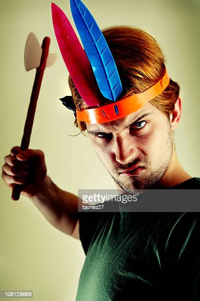 Man Wearing Toy Indian Head Dress and Holding Axe