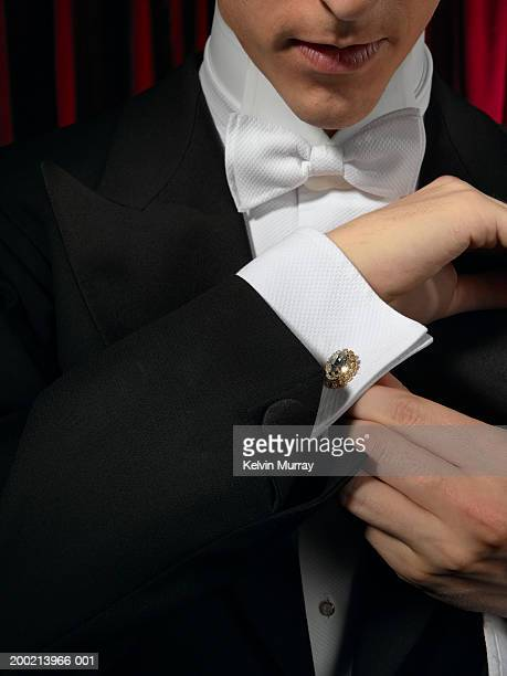 Man wearing tuxedo, adjusting cufflink, mid section, close-up