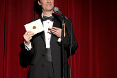 Man wearing tuxedo standing on stage, showing envelope, mid section