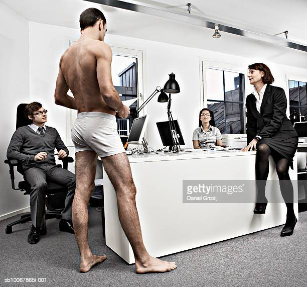 Man wearing underwear standing by business people gathered around office desk