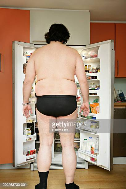 Man wearing underwear, standing by open fridge, rear view