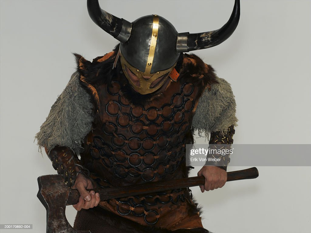 Man wearing warrior costume holding ax, bending over : Stock Photo