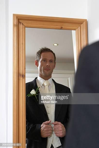Man wearing wedding suit, standing in front of mirror