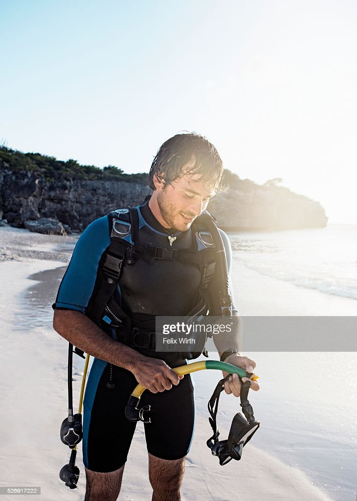 Man wearing wetsuit standing on beach : Stock Photo