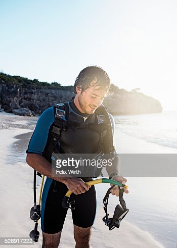 Man wearing wetsuit standing on beach : Stock-Foto