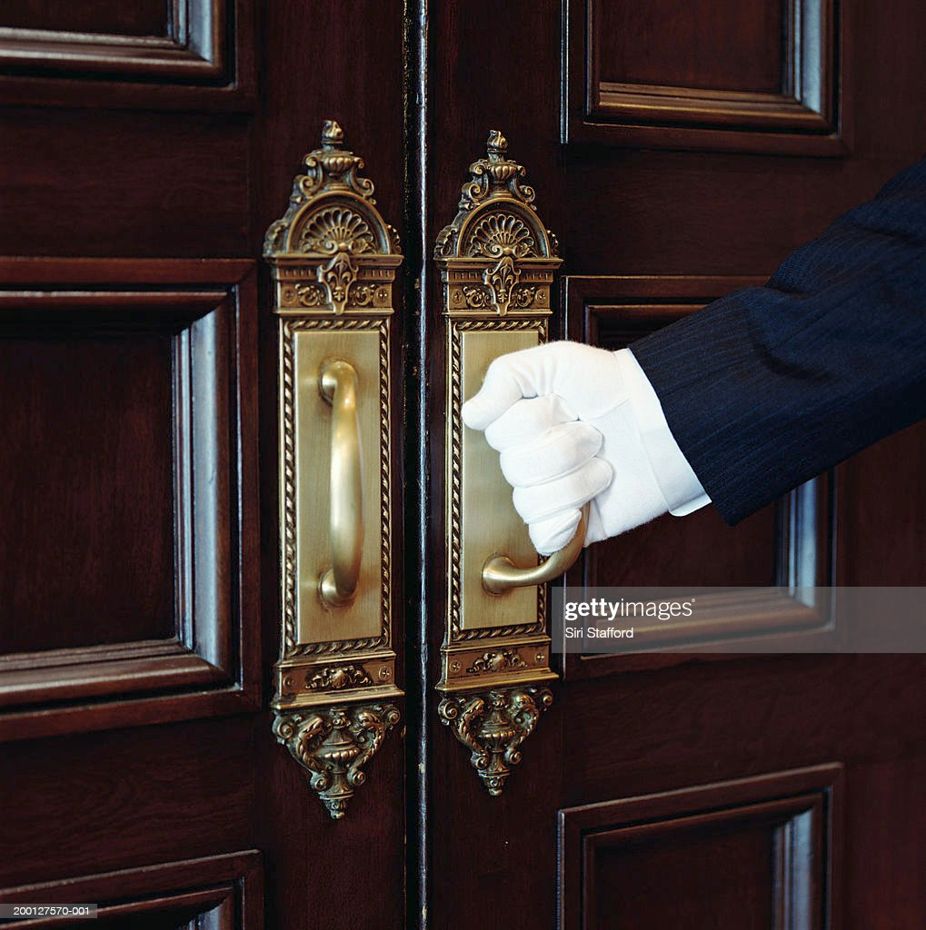 Man wearing white gloves, opening door, close-up : Photo