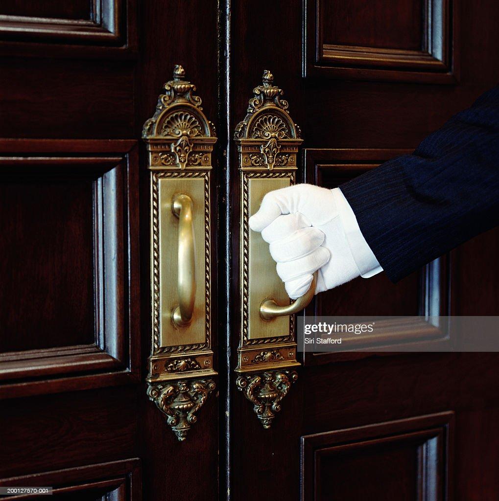 Man wearing white gloves, opening door, close-up