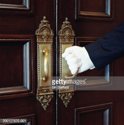 Man wearing white gloves, opening door, close-up : Stock Photo
