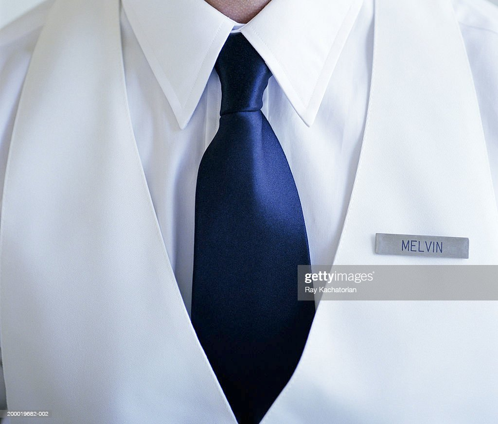Man wearing white shirt and blue tie with name tag : Stock Photo
