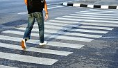 Man wearing white shoes and jean crossing the street crosswalk, Bangkok Thailand.