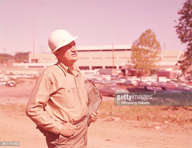 Man wearing work clothes and hard hat, holding clipboard, on construction site.