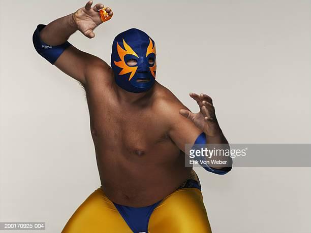 Man wearing wrestler costume and mask, in wrestling position