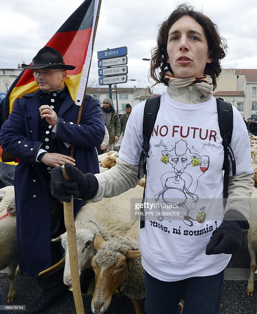 A man wears a a tea-shirt reading 'No future, neither chips, nor subdued' as French and German shepherds demonstrate with a flock of ewes, on February 1, 2013, in a street of Valence, southeastern France, to protest against the electronics chip RFID (Radio Frequency Identification) system imposed on their animals. The shephards are protesting over the mandatory tracking of all of their animals with electronic chips after new European Union legislation passed to impose this on all animals born since 2010. AFP PHOTO / PHILIPPE DESMAZES