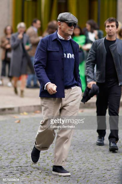 A man wears a beret hat a blue jacket a blue pull over beige pants blakc sneakers shoes outside Miu Miu during Paris Fashion Week Womenswear...