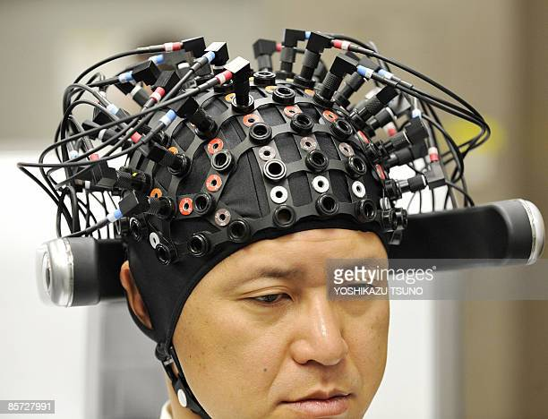 A man wears a brainmachine interface equipped with electroencephalography devices and nearinfrared spectroscope optical sensors in a special headgear...