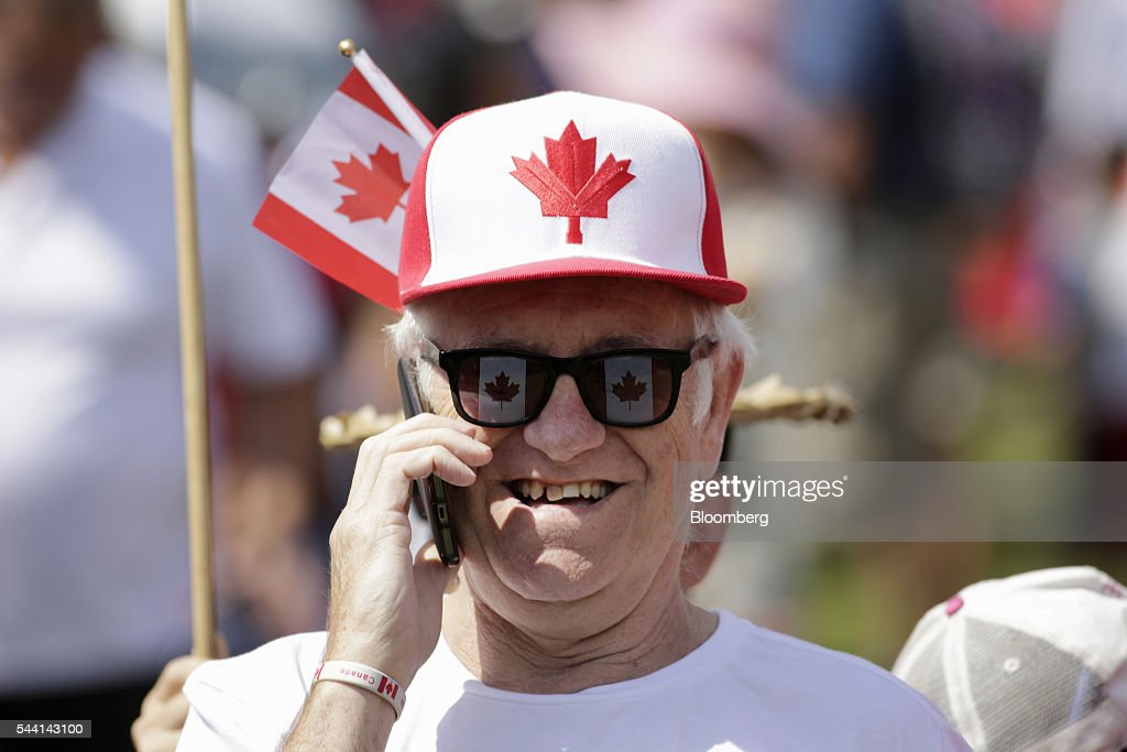 A man wears a Canadian flag themed hat while talking on mobile phone during Canada Day celebrations on Parliament Hill to begin, in Ottawa, Ontario, Canada, on Friday, July 1, 2016. On July 1, thousands of locals and tourists gather in Ottawa's downtown area to celebrate. This year marks Canada's 149th birthday and Trudeau's first Canada Day as Prime Minister. Photographer: David Kawai/Bloomberg via Getty Images