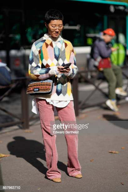 A man wears a colored wool pull over a bag pink pants outside Miu Miu during Paris Fashion Week Womenswear Spring/Summer 2018 on October 3 2017 in...
