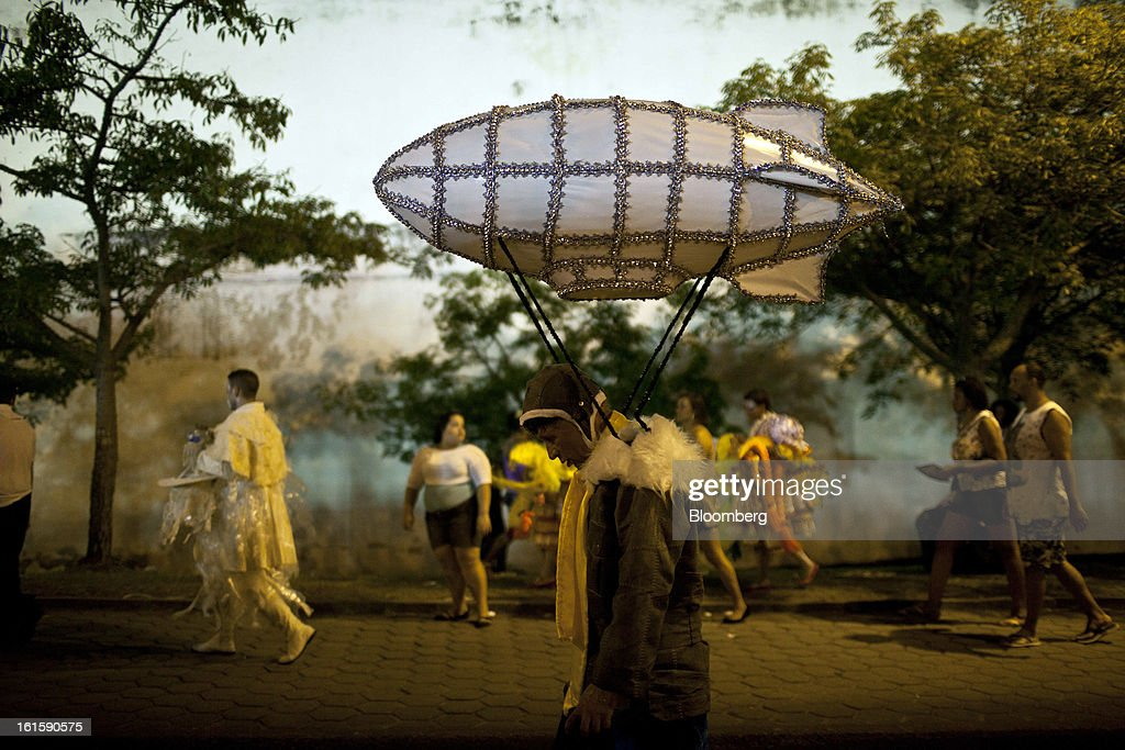 A man wears a costume with headgear designed like a blimp as he leaves the Sambadrome with other revelers during Carnival celebrations in Rio de Janeiro, Brazil, Monday, on Feb. 11, 2013. The festivities, which are expected to attract almost 900,000 visitors, precede the start of Lent, which begins with Ash Wednesday on Feb. 13. Photographer: Dado Galdieri/Bloomberg via Getty Images