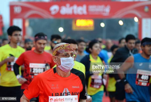 A man wears a face mask as he runs during the Airtel Delhi Half Marathon 2017 in New Delhi on November 19 2017 / AFP PHOTO / SAJJAD HUSSAIN