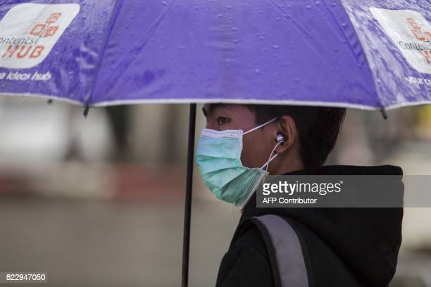 A man wears a face mask whilst waiting for a bus in Yangon on July 26 2017 Two people including a pregnant woman have died from swine flu in Yangon...