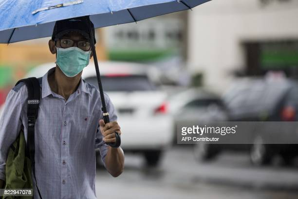 A man wears a face mask whilst walking on the street in Yangon on July 26 2017 Two people including a pregnant woman have died from swine flu in...