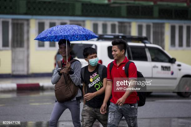 A man wears a face mask whilst walking with friends in Yangon on July 26 2017 Two people including a pregnant woman have died from swine flu in...
