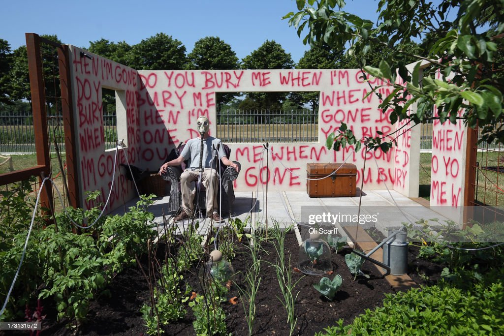 A man wears a gas mask as he sits in the 'I Disappear' garden at the Hampton Court Palace Flower Show on July 8, 2013 in London, England. Hampton Court Palace Flower Show opens to the public tomorrow and runs until July 14, 2013. It is the world's largest flower show with over 600 exhibitors spread over 34 acres.