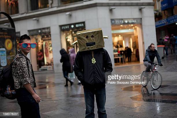 A man wears a gift box on the head at a shopping area in Central Madrid on December 14 2012 in Madrid Spain Many businesses are starting sales and...