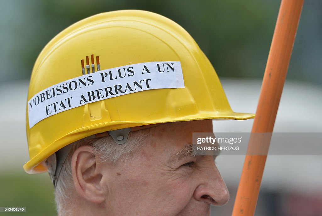A man wears a helmet reading 'Let's not obey to a ludicrous state' during a demonstration against controversial labour reforms, on June 28, 2016 in Strasbourg, eastern France. Unions have called repeated strikes and marches against controversial labour reforms, forced through by the government of Socialist President Francois Hollande. / AFP / PATRICK