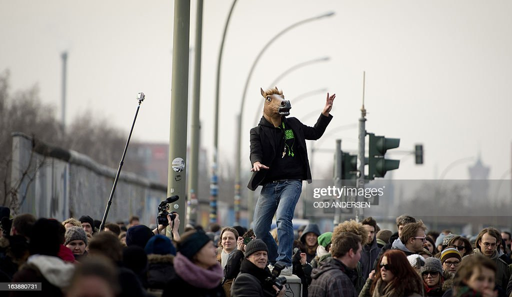A man wears a horse mask as he moves with the crowd to follow David Hasselhoff (not in pic) who tours the East Side Gallery on March 17, 2013 to protest the demolition of parts of the wall for a real estate project. The former Bay watch star was in the German capital to lend his support to the movement that wants to preserve the 1,3km long stretch of the cold war symbol and keep the land along river Spree as public land.