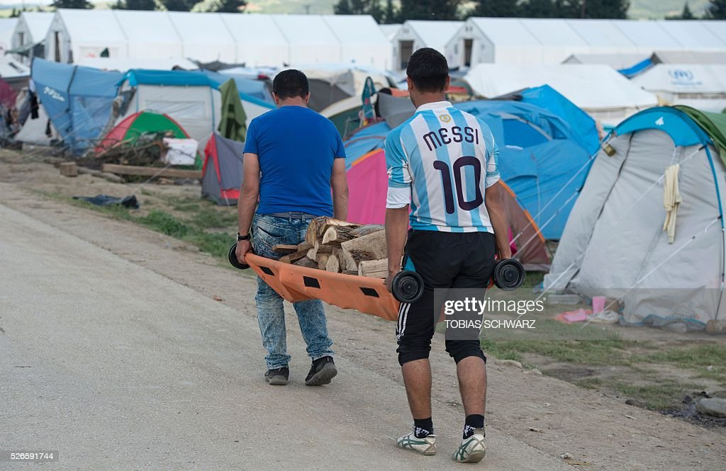 A man wears a jersey of Argentinian footballer Lionel Messi as he and another man carry fire wood with a stretcher at a makeshift camp for migrants and refugees near the village of Idomeni not far from the Greek-Macedonian border on April 30, 2016. Some 54,000 people, many of them fleeing the war in Syria, have been stranded on Greek territory since the closure of the migrant route through the Balkans in February. / AFP / TOBIAS