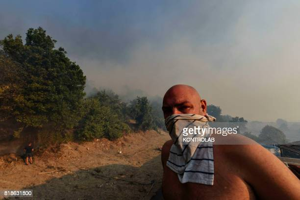 A man wears a mask as he stand on the roof of his house and look towards smoke on the horizon during a vast fire that threatened the inhabited areas...