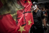 A man wears a mask of the Anonymous hacker group as he and other people take part in a protest for the cause of late Chinese dissident Li Wangyang in...