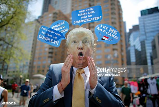 TOPSHOT A man wears a mask with the face of US President Donald Trump as he takes part in the '100 Days of Failure' Protest to mark the first 100...