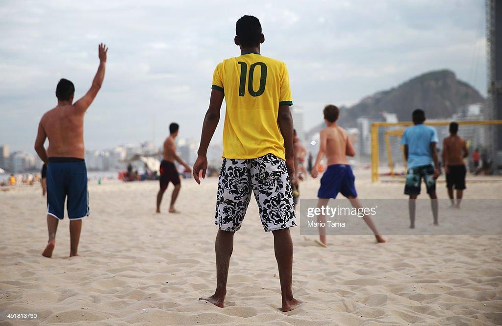 A man wears a Neymar jersey as Brazilians play soccer on Copacabana Beach on July 7, 2014 in Rio de Janeiro, Brazil. Brazil plays Germany tomorrow in the first semi-final match of the 2014 FIFA World Cup.