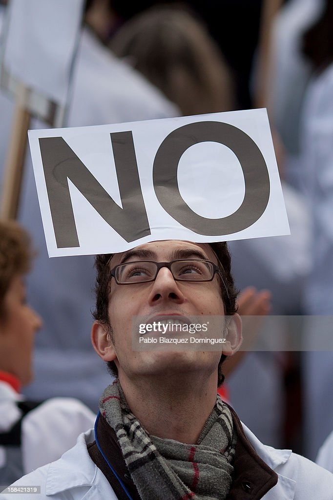 A man wears a placard that reads 'No' amid other health workers during a demonstration against cuts on public health care and the privatization of medical centers and hospitals on December 16, 2012 in Madrid, Spain. In Madrid, doctors have already staged 11 days of strikes and all health workers unions are calling for a third 48 hour strike on December 19 and December 20. Around 4,000 operations have been suspended in Madrid since the medical strikes started.