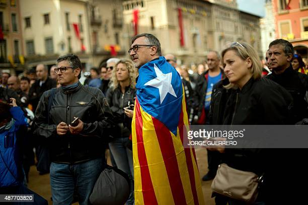 A man wears a pro independence Catalan flag as he takes part in celebrations of Catalonia National Day that recalls the final defeat of local troops...