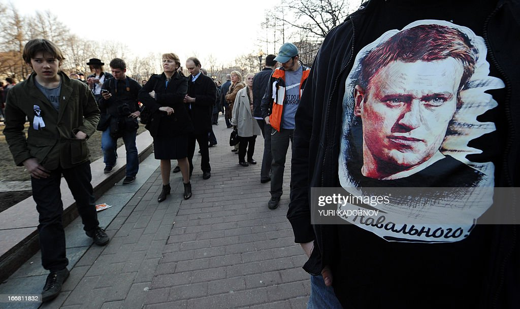 A man wears a tee-shirt with a picture of Russian protest leader Alexei Navalny during an opposition rally in his support in central Moscow on April 17, 2013.Russian opposition leader Alexei Navalny went on trial Wednesday on charges he says were ordered by President Vladimir Putin to eliminate a top opponent, but the process was swiftly adjourned for a week to allow the defence more time to prepare.