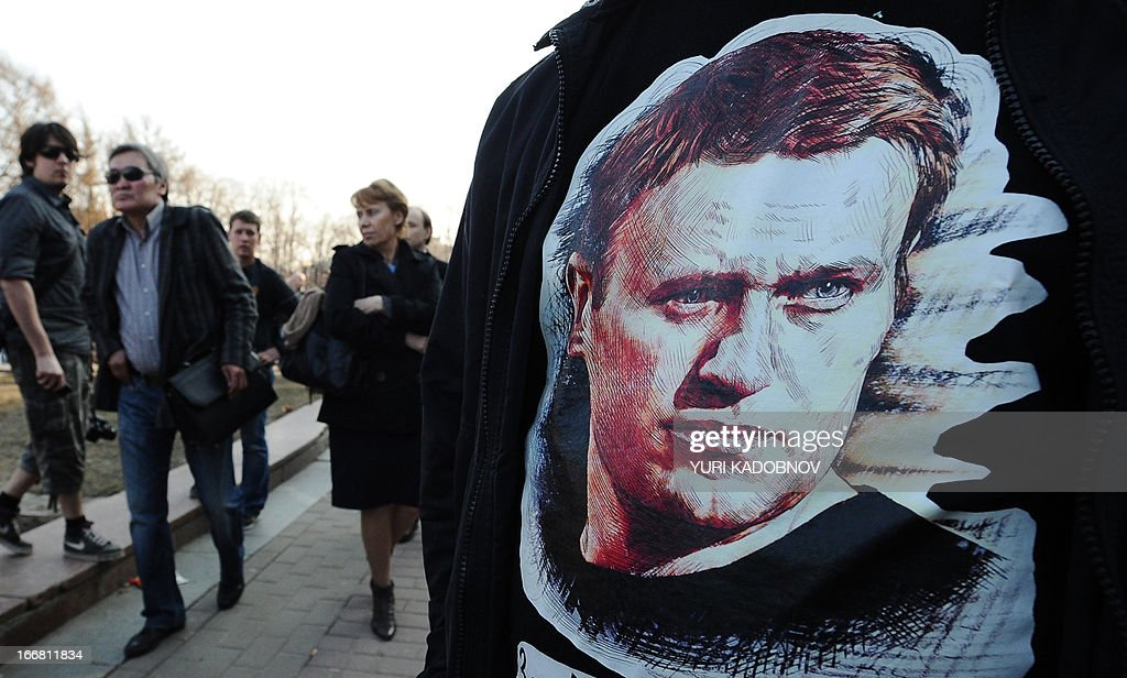 A man wears a tee-shirt with a picture of Russian protest leader Alexei Navalny during an opposition rally in his support in central Moscow on April 17, 2013. Russian opposition leader Alexei Navalny went on trial Wednesday on charges he says were ordered by President Vladimir Putin to eliminate a top opponent, but the process was swiftly adjourned for a week to allow the defence more time to prepare. AFP PHOTO / YURI KADOBNOV