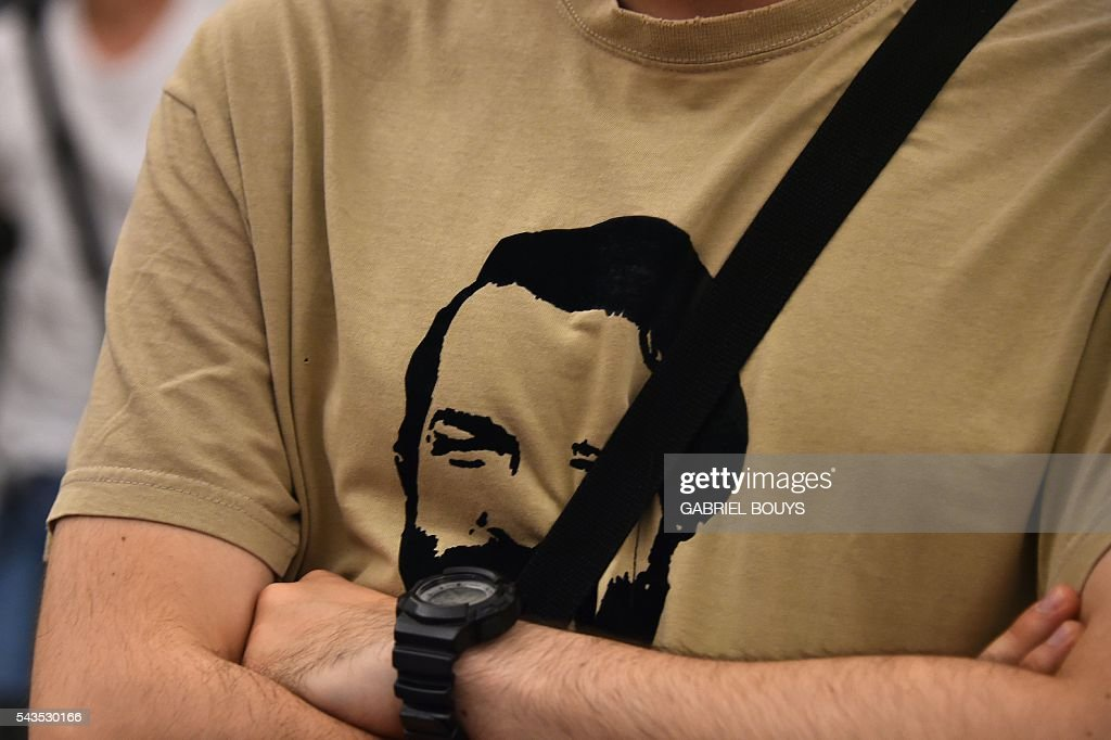 A man wears a tee-shirt with a portrait of actor Bud Spencer as people pay their respects in front of his coffin lying in repose at Rome's city hall. Bud Spencer who starred in a string of spaghetti westerns, died on June 27 in Rome aged 86, his family confirmed. Spencer, born Carlo Pedersoli in Italy in 1929, played in 16 films alongside Terence Hill, whose real name was Mario Girotti. / AFP / GABRIEL