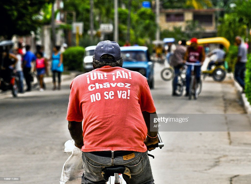 A man wears a T-shirt reading 'Chavez wont's leave' as he rides a bicyle, on January 3, 2013 in Havana. Venezuelan Vice-President Nicolas Maduro recently acknowledged that the president is in a delicate situation due to postoperative problems. Top Venezuelan officials gathered in Cuba on Thursday amid growing demands for news about cancer-stricken President Hugo Chavez' condition, days before he is to be sworn in for another term.