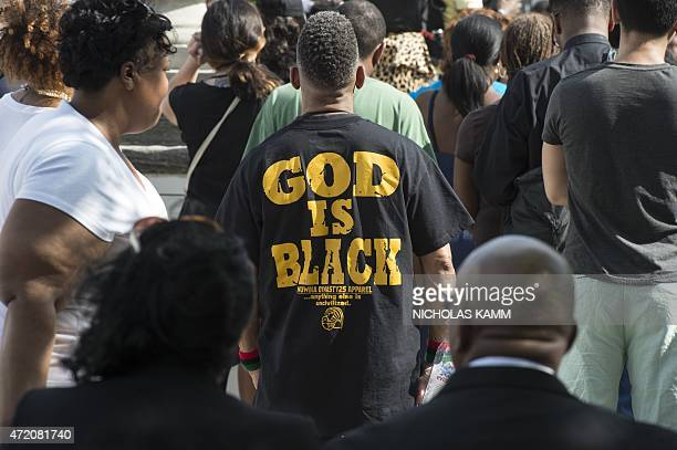 A man wears a Tshirt reading 'God IS Black' during a rally in front of City Hall in Baltimore Maryland on May 3 2015 calling for peace following...