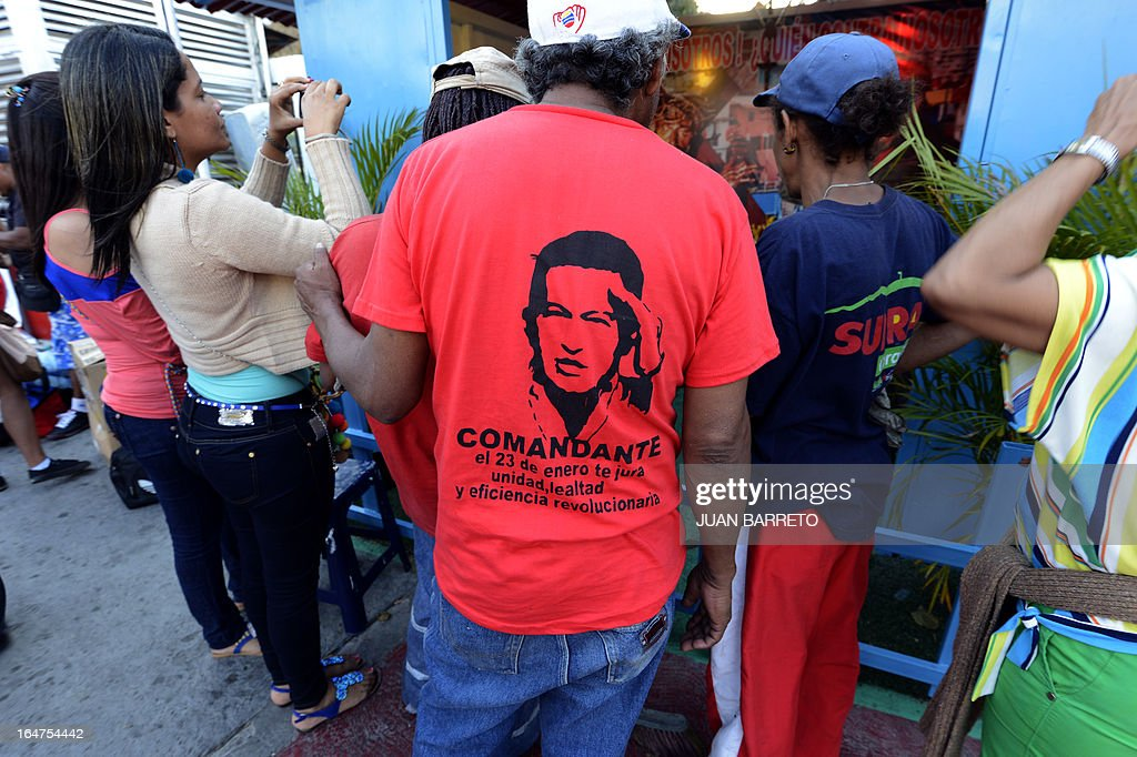 A man wears a T-shirt with the portrait of late Venezuelan President Hugo Chavez as residents take pictures of newly inaugurated Santo Hugo Chavez del 23 chapel, at the 23 de Enero neighbourhood, in the surroundings of the museum where his remains lay, in Caracas on March 27, 2013. AFP PHOTO/JUAN BARRETO