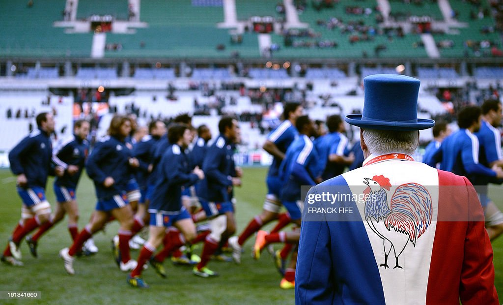 A man wears a vest featuring the French flag colors and French rooster symbol as the France's national rugby team's player run during a training before the Six Nations Rugby Union match between France and Wales at the Stade de France on February 9, 2013 in Saint-Denis, north of Paris.