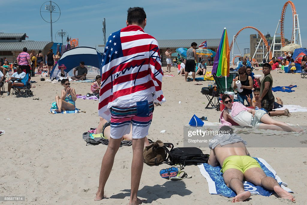 A man wears an american flag towel during a day at the beach in Coney Island on May 29, 2016 in the Brooklyn borough of New York City. New York City is experiencing higher than average temperatures for the holiday weekend.