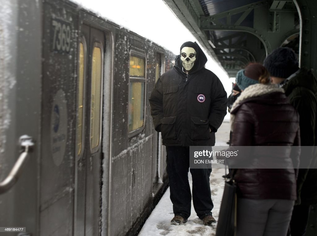 A man wears an unusual mask to protect himself from the cold as he waits for a train at a subway station February 13, 2014 in New York. Up to a foot (30 cm) of snow is expected in the New York area. AFP PHOTO Don Emmert