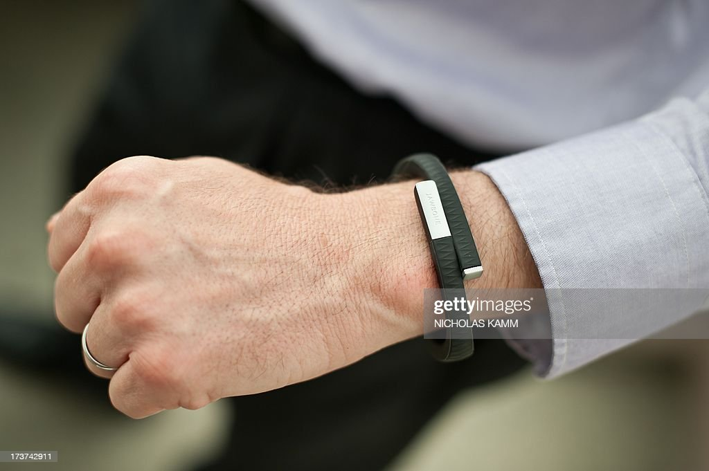 A man wears an UP fitness wristband in Washington on July 16, 2013. Jawbone, the San Francisco-based company behind 'smart' wireless earpieces and Jambox speakers, late last year released redesigned UP wristbands that combine fashion with smartphone lifestyles to help people along paths to improved fitness. UP wristbands are priced at $129 in the United States. UP applications tailored for Apple or Android mobile devices collect data from the bands to let people get pictures of activity, sleep, eating, and even moods on any given day or over time. AFP PHOTO/Nicholas KAMM