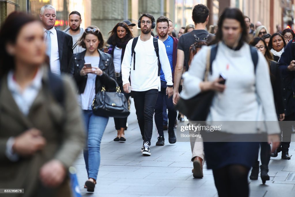 A man wears headphones as he and other commuters walk through Martin Place in Sydney, Australia, on Thursday, Aug. 17, 2017. Australian employers added more jobs than forecast in July, underscoring the central banks confidence in an improving labor market. Photographer: Brendon Thorne/Bloomberg via Getty Images