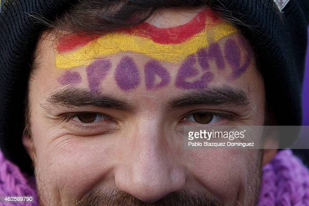 A man wears paint reading 'We can' during a march of Podemos political party on January 31 2015 in Madrid Spain According to the last opinion polls...